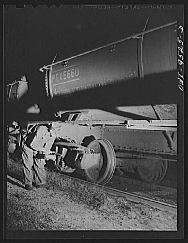 Tulsa, Oklahoma. Yard employee inspecting the wheels of an oil tank car