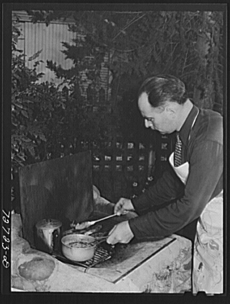 Turlock, California. Man of the house barbecues steaks over open grill in the backyard