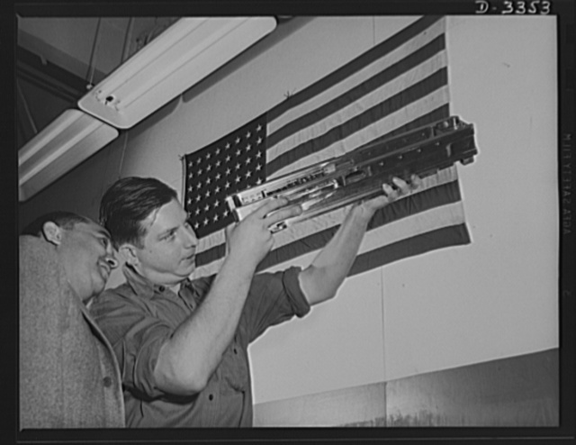 Twenty-millimeter machine guns for planes. A former automotive worker in a converted auto plant sights through the precision-made breech of a machine gun for the Air Corps. One of thousands of examples of the way American enterprise threw its technical skill and its tremendous mass production facilities behind the war production drive. Oldsmobile, Lansing, Michigan