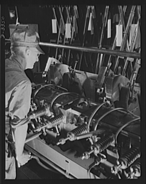 Twenty-millimeter machine guns for planes. A production lathe in a former auto plant and an experienced automobile worker team up to give our air force the greatest possible number of the finest possible machine guns. Oldsmobile, Lansing, Michigan
