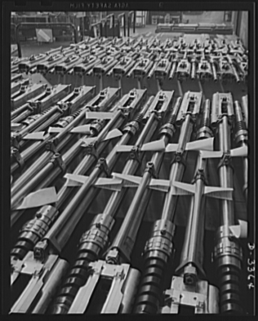 Twenty-millimeter machine guns for planes. American power in the air grows rapidly as machine guns of the finest quality pour from our production lines to arm the planes that are coming steadily from other lines. These guns, entirely completed and ready to fire, await shipment from the large converted auto plant in which they were made. Oldsmobile, Lansing, Michigan