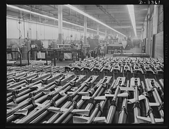Twenty-millimeter machine guns for planes. American power in the air grows rapidly as machine guns of the finest quality pour from production lines to arm the planes that are coming steadily from other lines. These guns, entirely completed and ready to fire, await shipment from the large converted auto plant which made them. Oldsmobile, Lansing, Michigan
