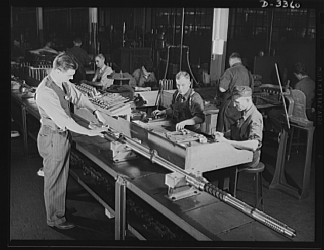 Twenty-millimeter machine guns for planes. An assembly line in a converted auto plant, now turning out machine guns for the Air Corps, comes through with plenty of these important tools of war. And the tide of American productive power is still far from being reached. Oldsmobile, Lansing, Michigan