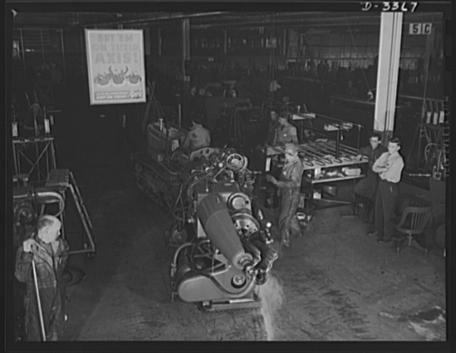 Twenty-millimeter machine guns for planes. Another machine is skidded into place in a converted auto plant to swell the production of machine guns for the Air Corps. Oldsmobile, Lansing, Michigan