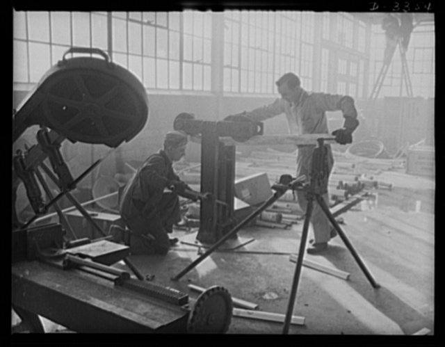 Twenty-millimeter machine guns for planes. The conversion of a big auto manufacturing plant to production of machine guns for the Air Corps continues without letup until the job is done. Electricians extending power lines are often among the first at the new machine locations. Oldsmobile, Lansing, Michigan