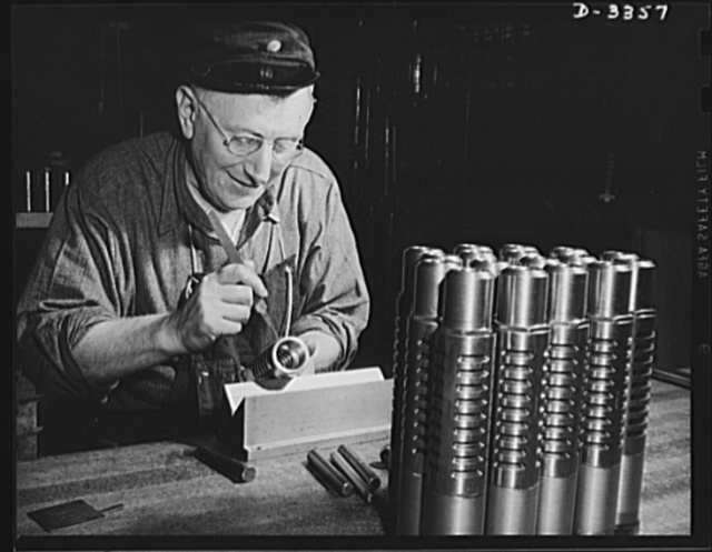Twenty-millimeter machine guns for planes. The muzzle break of a machine gun for the Air Corps must be right. An inspector in a big auto plant now converted to war work examines each piece as it travels down the production line. Oldsmobile, Lansing, Michigan