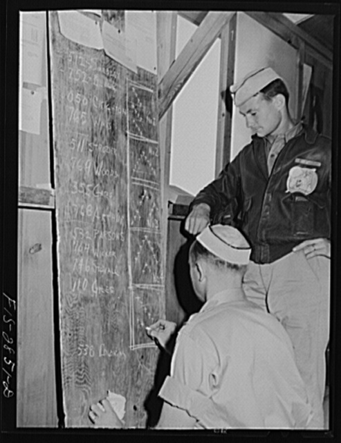 Two lieutenants of pursuit squadron map out the formations in which they will lead their flights. Lake Muroc, California