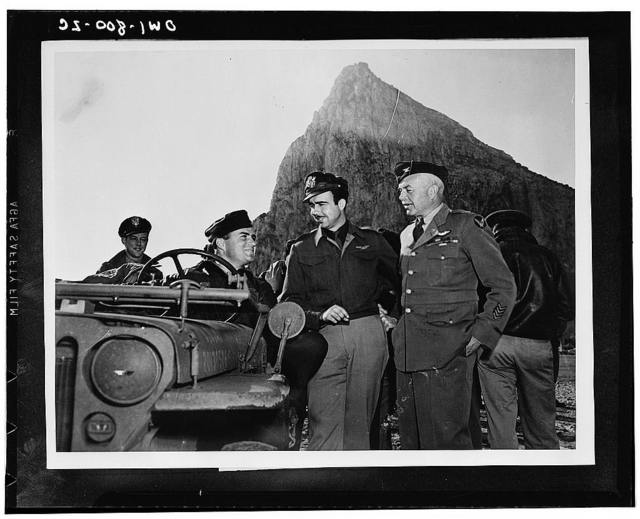 United States Army Air Force officers confering somewhere in the European theater of operation. At the wheel of the jeep is Major Marvin L. McNickle of Doland, South Dakota, with Captain E. A. Vinson of Monticello, Mississippi, and Colonel Harold B. Willis of Boston, Massachusetts