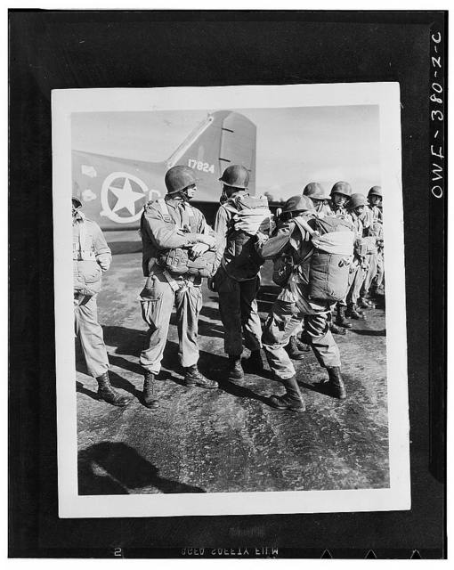U.S. paratroopers inspecting each others' parachutes before taking off on maneuvers somewhere in England. Note the camouflaged helmets