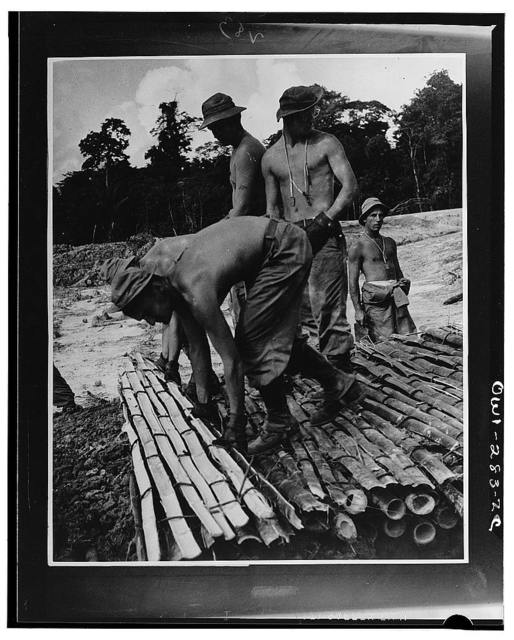 U.S. troops in the Caribbean area constructing a single-span stringer bridge of bamboo. They are spreading the mat over the second layer of clay