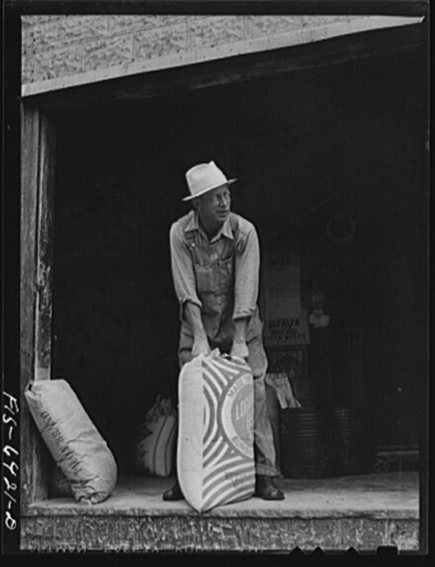 Vernon County, Wisconsin. Edward Saugstad with a bag of feed