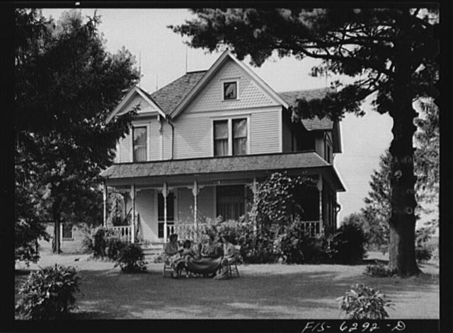 Vernon County, Wisconsin. Home of E.J. Saugstad. Mrs. Saugstad and neighbors are braiding a rug