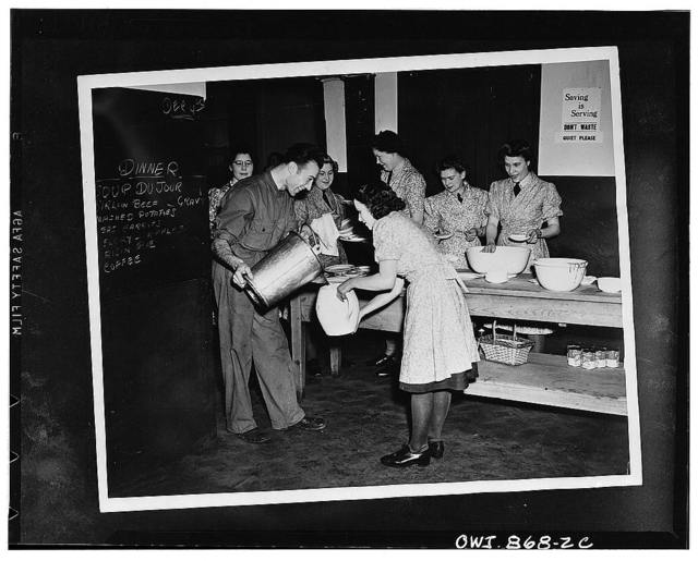 WAAFS -- England's women auxiliaries are assigned to assist United States task forces over there. Here they are shown preparing dinner for American troops at a mess hall somewhere in England.  Private First Class Rocco Pagliano of Providence, Rhode Island, lending a hand