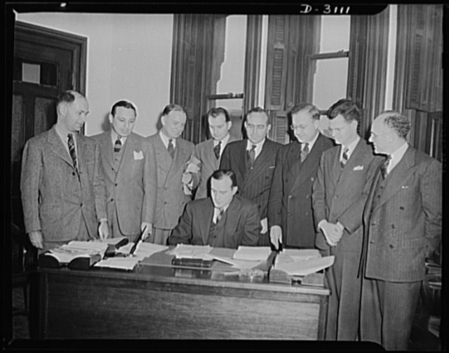 War Production Board Sugar Policy Committee. This shows the first meeting of the newly formed War Production Board Sugar Policy Committee. The committee consists of representatives of light government agencies concerned with the sugar problem. The committee was formed to exchange information and to recommend and formulate programs for the correlation of the activities of the various agencies concerned with the sugar problem. A. E. Bowman, Chief of the War Production Board Sugar Section is Committee Chairman. He is seated in the center. Other members are from left to right: Philip Nichols, War Production Board attorney, who is secretary of the Committee; J. E. Brunner, War Shipping Administration; F. H. Rawls, U.S. Department of Commerce; J. H. Westing, Office of Price Administration (OPA); S. H. Sabin, Defense Supplies Corp.; Guy J. Swope, Department of the Interior; L. Duggan, State Department; and Dr. Joshua Bernhardt, Department of Agriculture