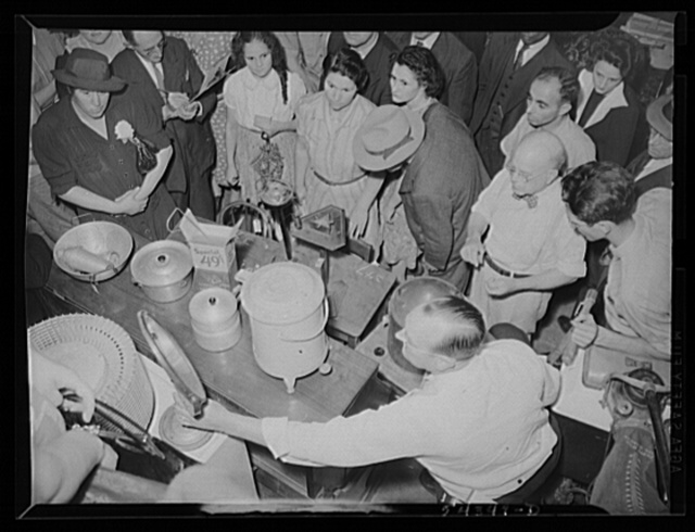Washington, D.C. A crowd surrounding an auctioneer selling kitchen utensils and other items at the Adam A. Weschler & Son auction store