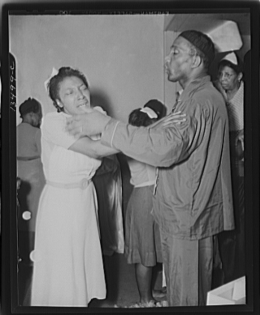 """Washington, D.C. A member of the St. Martin's Spiritual Church, receiving the final blessing of a flower from Reverend Vondell Gassaway, the pastor at the annual """"flower bowl demonstration"""""""