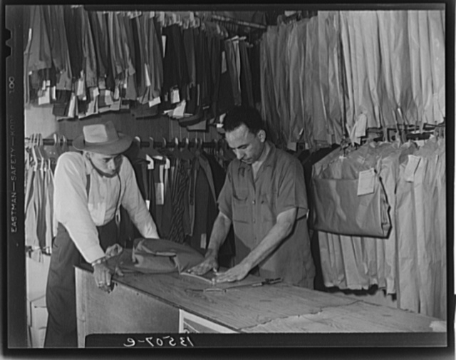Washington, D.C. A tailor in Frank's cleaning and pressing establishment altering a pair of pants for a customer
