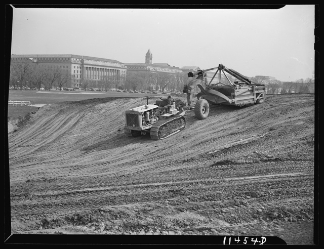 Washington, D.C. Construction of temporary war emergency buildings on the Mall, near 16th and 17th Streets, N.W. Le Tourneau earth mover and caterpillar tractor being used to move the top soil from the building site. The machine was also used to dig the basements