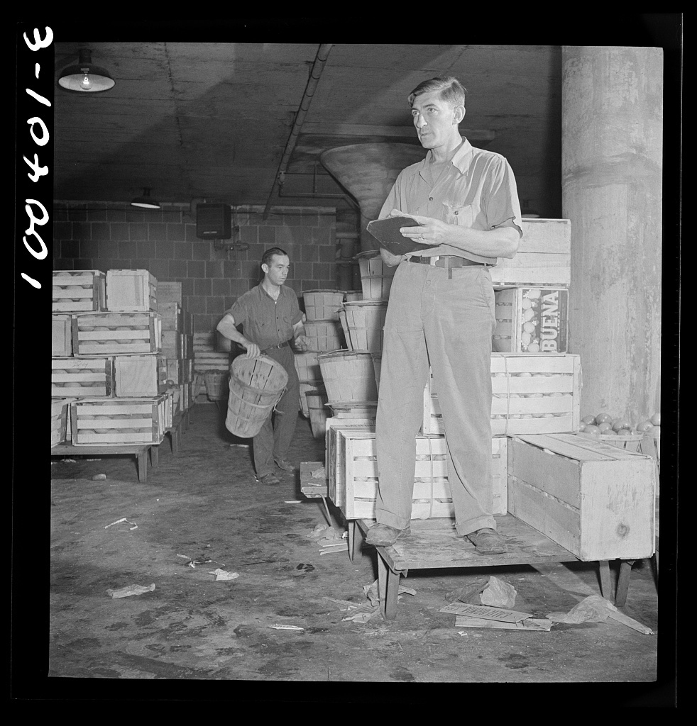 Washington, D.C. District grocery store warehouse on 4th Street S.W. Foreman calling out orders from the platform, which men are loading onto small trucks