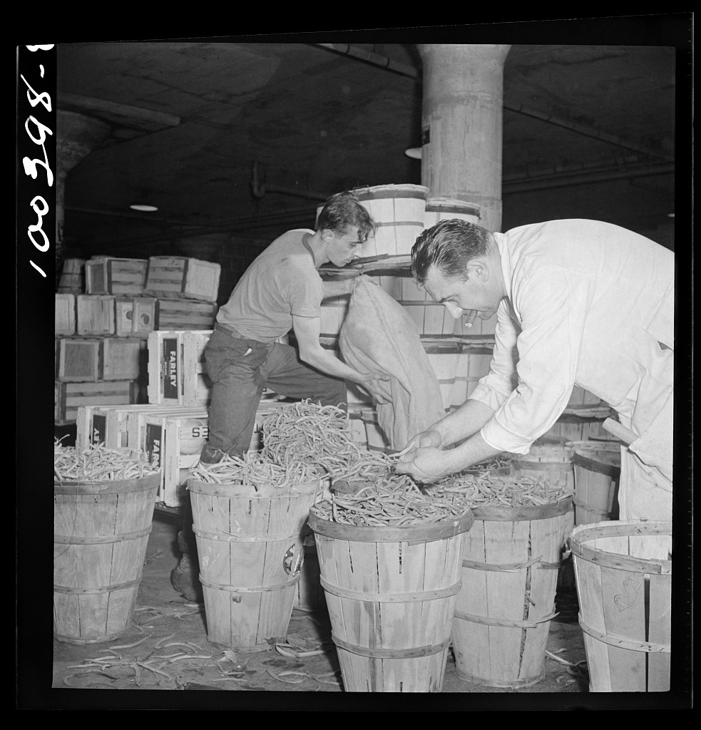 Washington, D.C. District grocery store warehouse on 4th Street S.W. Produce department. Assistant department head checking over string beans