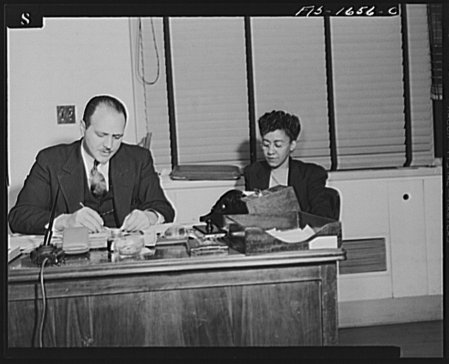 Washington, D.C. Doctor Robert C. Weaver, Chief of the Minority Groups, Bureau of Placement, War Manpower Commission, until February 1944, when he went to Chicago to become codirector of the mayor's interracial committee, set up on racial relations following the Detroit riots. Shown with a secretary, Miss Mary Pipes, of the War Manpower Commission, Bureau of Placement
