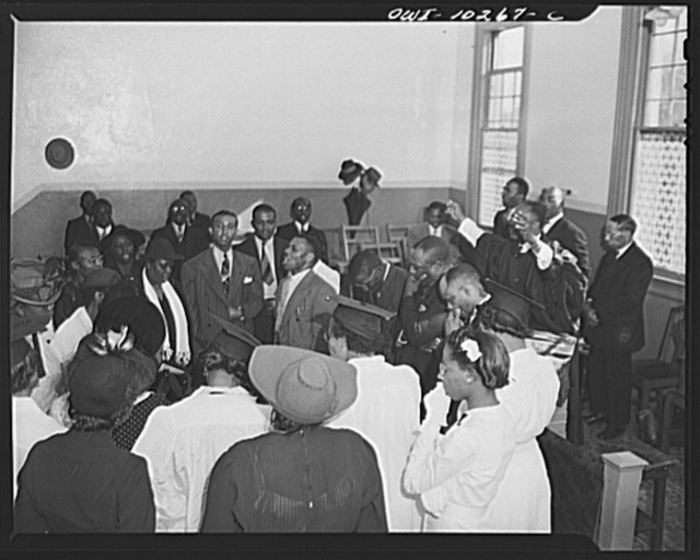 Washington, D.C. Elder Kelsey, pastor of the Church of God in Christ, blessing his Sunday morning congregation