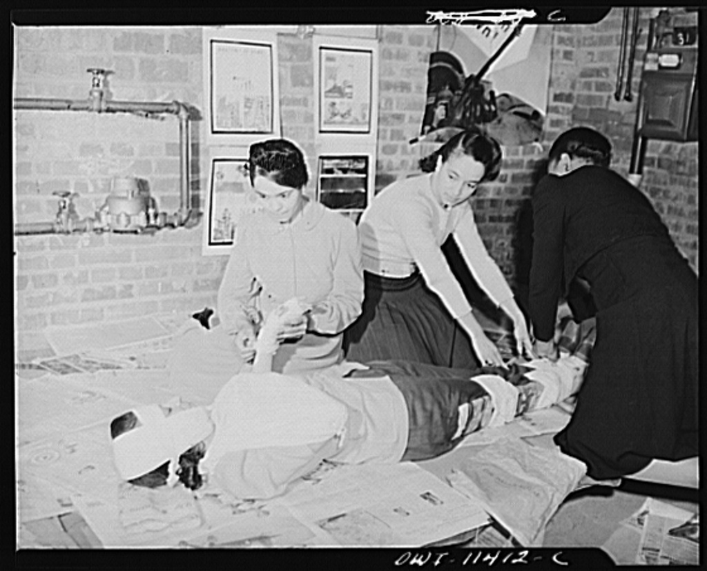 Washington, D.C. First aid class of the air raid warden unit in the Southwest area. Three members of the class applying splints, hand, head and arm bandages to a member of the class