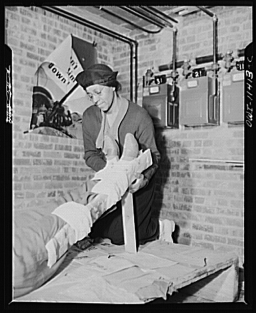 Washington, D.C. First aid class of the air raid warden unit in the Southwest area. An elderly member of the first aid class adjusting the legs to the proper position after applying splint