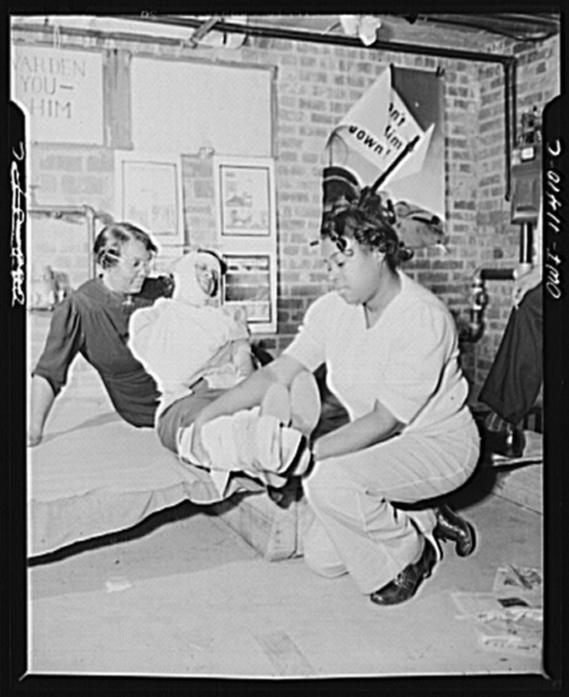 Washington, D.C. First aid class of the air raid warden unit in the Southwest area. Two members of the class applying splints and other bandages to a practice victim