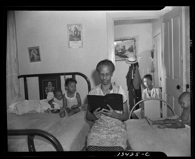 Washington, D.C. Mrs. Ella Watson, a government charwoman, reading the Bible to her household
