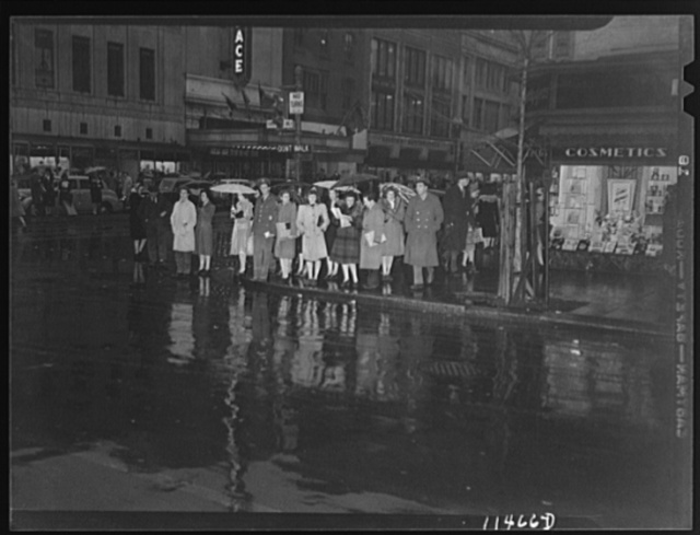 "Washington, D.C. People on a rainy night at 13th Street and F Street, N.W. waiting for the ""Don't walk"" neon traffic light to signal ""Walk"""