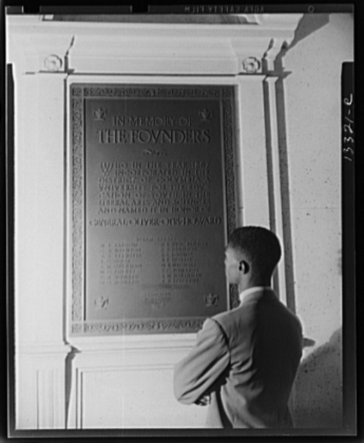 Washington, D.C. Student reading bronze plaque in library of Howard University