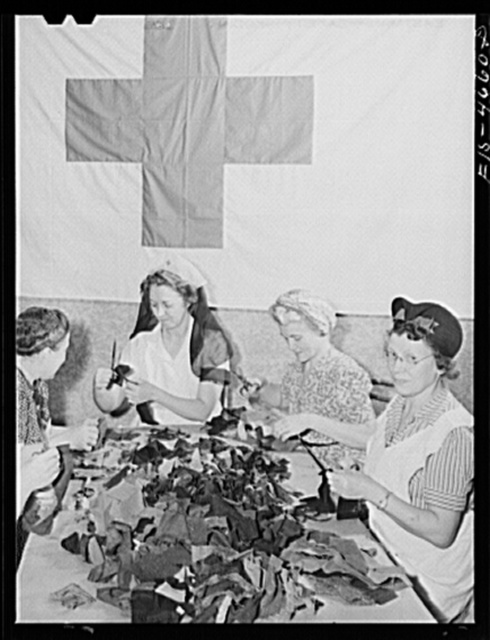 Washington, D.C. The District Red Cross is collecting, as part of the war conservation program, scraps of wool from tailors, manufacturers, and individuals. Here a group of volunteer women are sorting them and cutting off the threads to prepare the wool for reprocessing. There is a nationwide drive to eliminate trouser cuffs and other unnecessary parts of garments