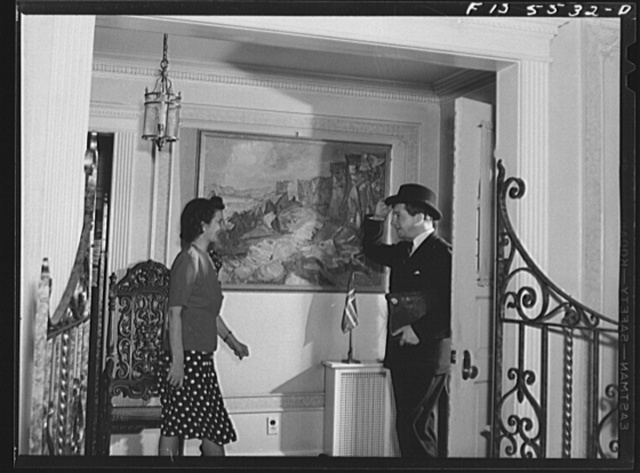 Washington, D.C. The Icelandic legation. Mrs. Thors greeting her husband as he returns from official business at the State Department. On the hall wall is a scene in Iceland painted by a well-known artist. Beneath it is the Icelandic flag