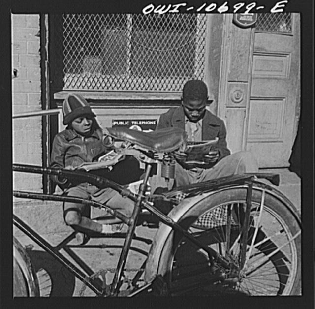 Washington, D.C. Two Negro boys reading the funnies on a doorstep