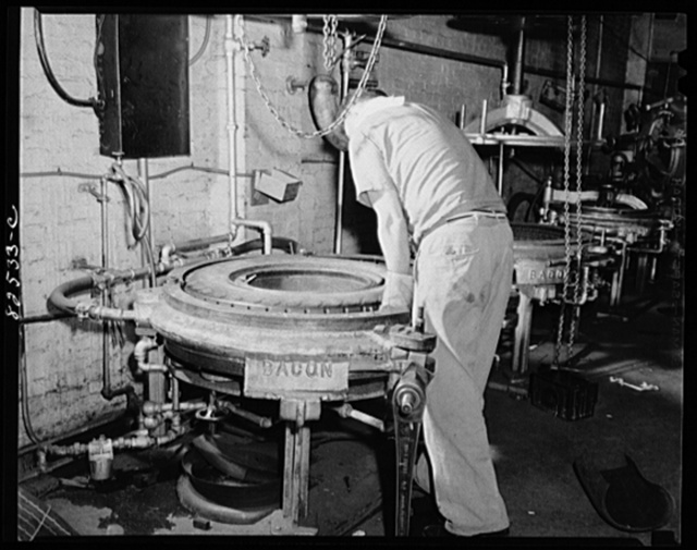 """Washington, D.C. Washington tire store. Settling tire in vulcanizing mould where it will """"cook"""" for three hours to """"cure"""" the recap onto the old tire"""