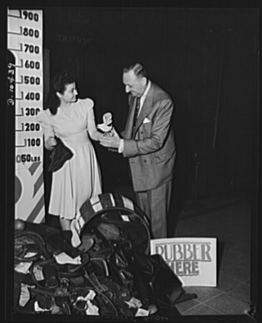 Washington Irving High School rubber salvage drive, New York City. Chairman of New York City salvage committee, Clarence H. Low, with Susan Balint, Washington Irving High senior gathering the various rubber articles donated by school kids after an intensive rubber treasure attic from attic to cupboard in their own homes