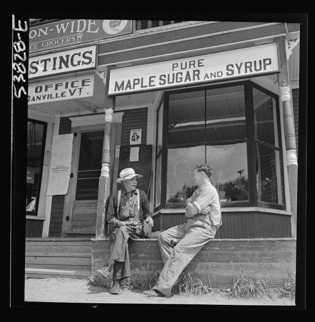 """West Danville, Vermont. In front of Gilbert S. Hastings General Store and post office, Floyd Wheeler, clerk, chatting a moment in the sunshine with W.D. Coolbeth, seventy-two year old retired farmer. A sign reading """"Pure maple sugar and syrup"""" hangs over the porch of the store"""