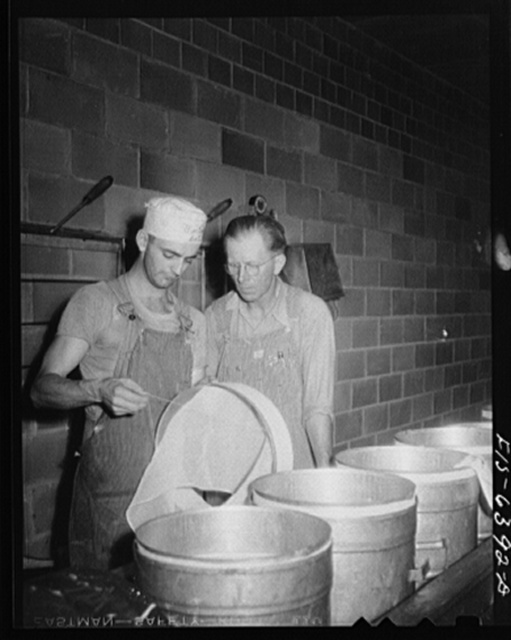 Westby, Vernon County, Wisconsin. Cheesemaker showing Saugstad how cheesecloth is applied at the cooperative creamery