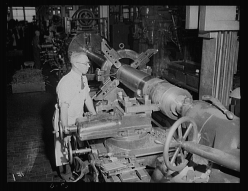 Where there's smoke... A worker in an eastern arsenal turns the thread surface on a medium-caliber gun. Note the wisp of smoke rising from the point where the thread is being cut