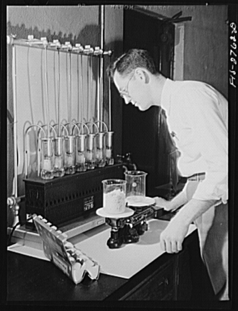 William J. Shannon, PhD, assistant professor in chemistry. He is in charge of food chemistry at Iowa State College. He is here working on dried whole eggs used in lend lease shipments. The dried eggs in the beaker are equal to one dozen whole eggs. Iowa State College, Ames, Iowa