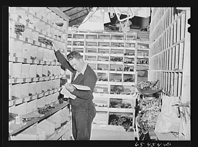 Wisdom, Montana. Len Smith in the stockroom of the Basin Mercantile Company. They have an extremely large stock of tractor and haying machine parts
