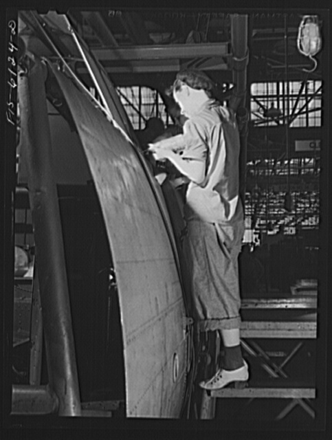 Woman riveter at work on the fuselage of a bomber at the Vultee Aircraft Corporation plant