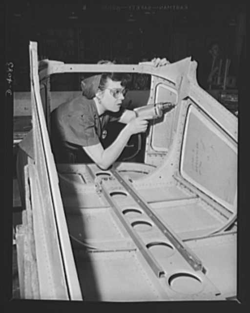 Women aircraft workers. She can't forget Pearl Harbor, and she's determined that Hitler and Hirohito shall have cause to remember it. Mrs. Evelyn J. W. Casola, Pearl Harbor widow, drills rivet holes in the belly gun door of a U.S. bomber, soon to storm over Axis lands, showing death to the aggressors