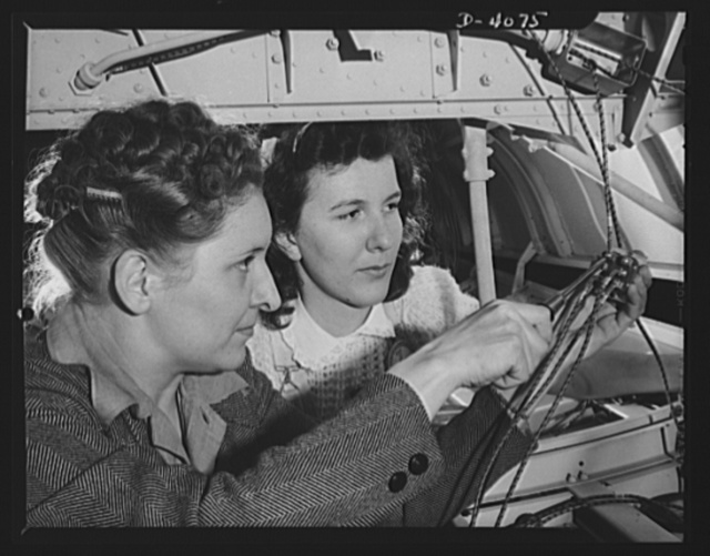 Women aircraft workers. The epitone of determination and industry is personified in these two women employees of a large West Coast airplane factory. Down underneath a giant bomber, a woman electrician and her helper are making electical installations in the bomb bay. Vega