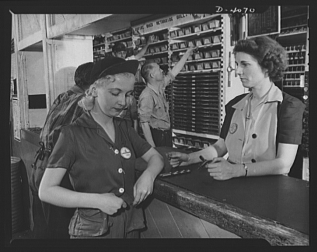 Women aircraft workers. Women work on both sides of the counter at this West Coast aircraft factory. A drill press operator here swaps a tool check for a drill which is given to her by one of the tool crib keepers. Lockhead