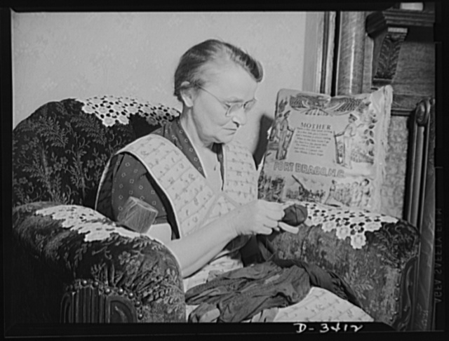 Women at war (Mrs. Smuda). If you didn't know better, you might think Mrs. Smuda spent the day comfortably darning socks for the family. Less than an hour before these pictures were made, this fifty-five-year-old mother and grandmother was skillfully tapering shells for machine guns at the Frankford Arsenal