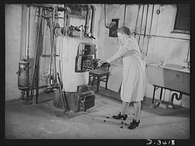 Women at war (Mrs. Smuda). She gives half her day to Uncle Sam and the other half to her home and family. Firing the furnace looks like a man-sized job, but Mrs. Smuda has reduced it to a system. Note that short handled shovel to make the job easier