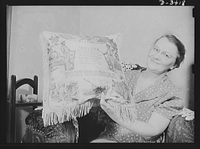 "Women at war (Mrs. Smuda). ""The sweetest lady I ever met.. Dear Mother, I won't forget."" So reads this pillow, sent Mrs. Smuda by her youngest son now at camp. But unlike Whistler's immortalized parent, the mother of the Smuda family spends little time in an armchair. She's much too busy working for Uncle Sam at the Frankford Arsenal and taking active care of her home and family after hours"