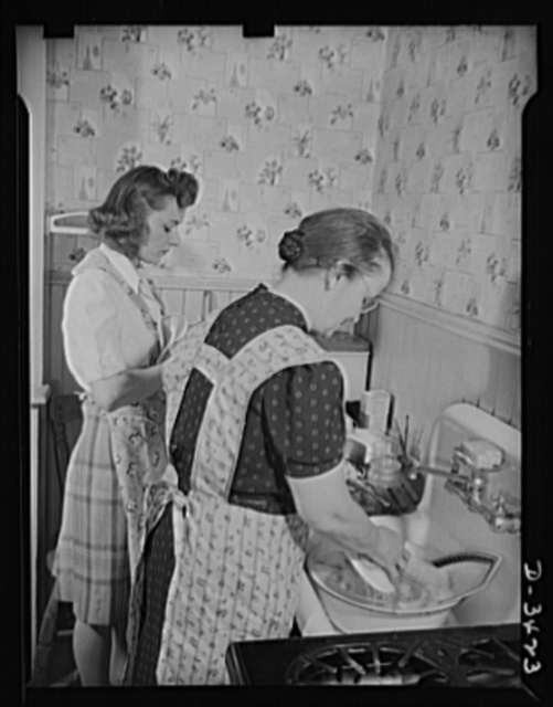 Women at war (Mrs. Smuda). There's a war to be won, but there's work to be done at home, and this modern warrior-mother enjoys taking a hand in household duties. Tonight, she's washing the supper dishes while her daughter Genevieve dries